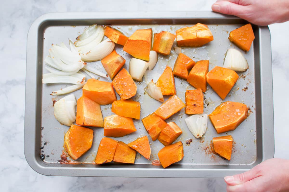 Baked pumpkin and onion on a tray.