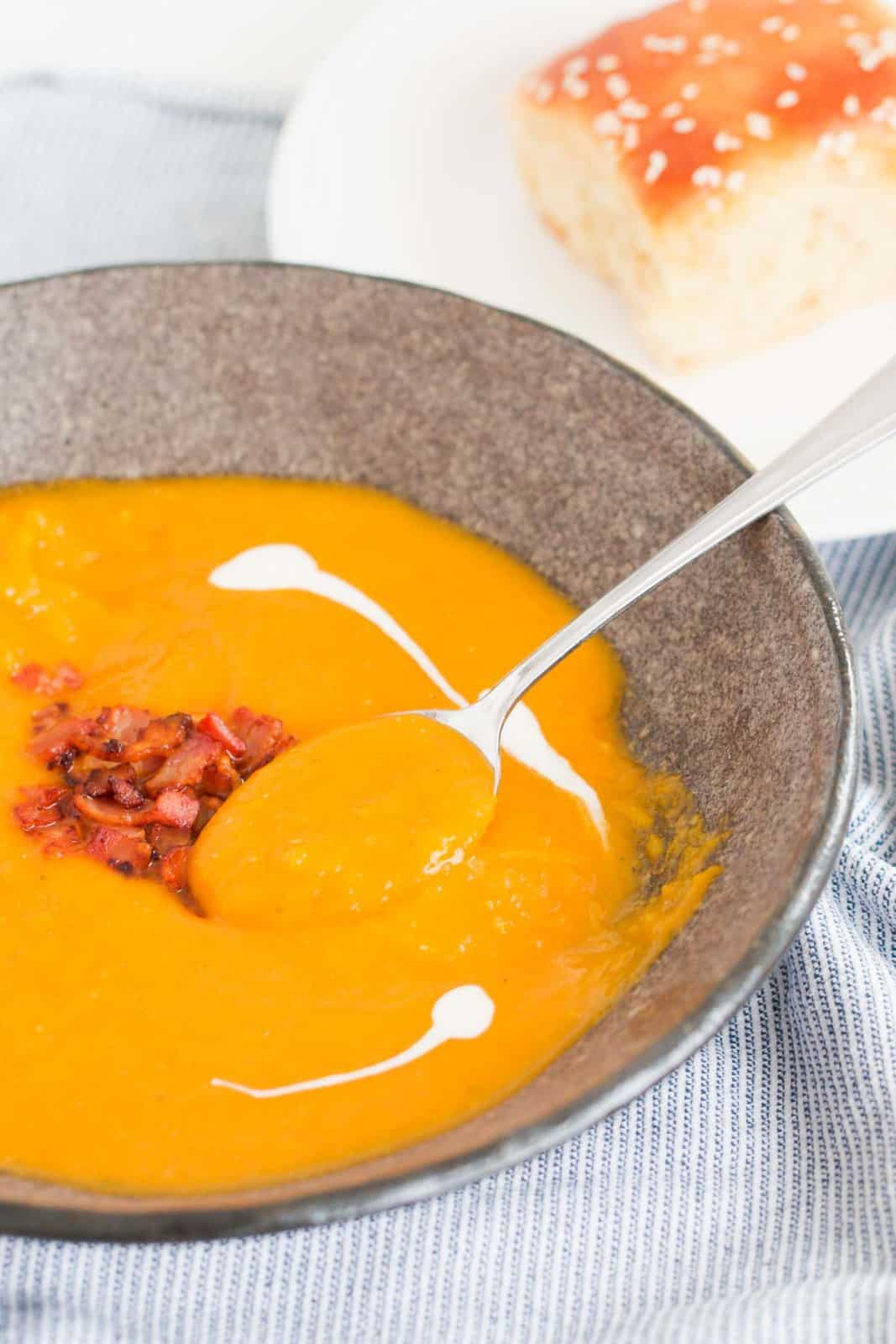 A spoon in a bowl of pumpkin soup with bacon and drizzled cream.