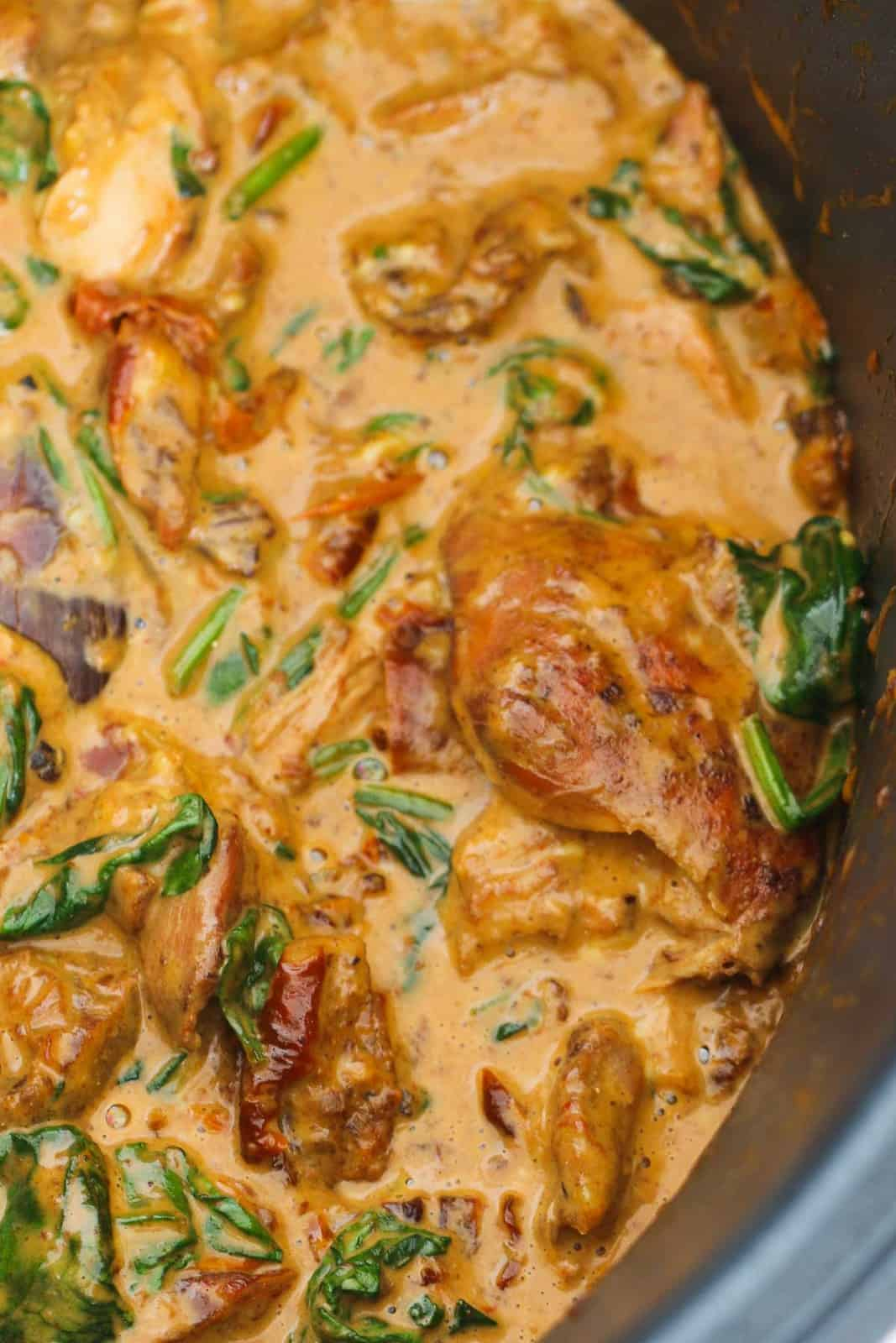 A slow cooker filled with creamy chicken, sundried tomatoes and spinach.