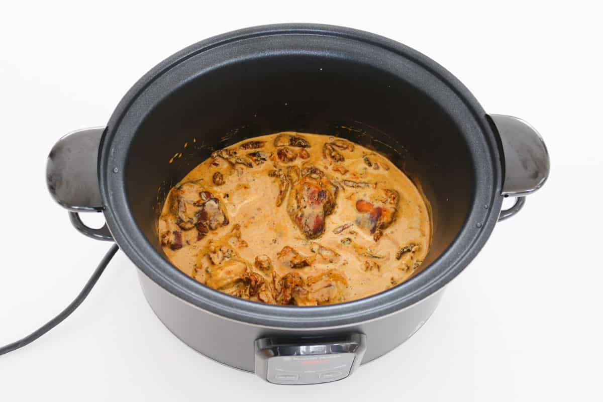 A creamy chicken, paprika and sundried tomato dish in a crockpot.