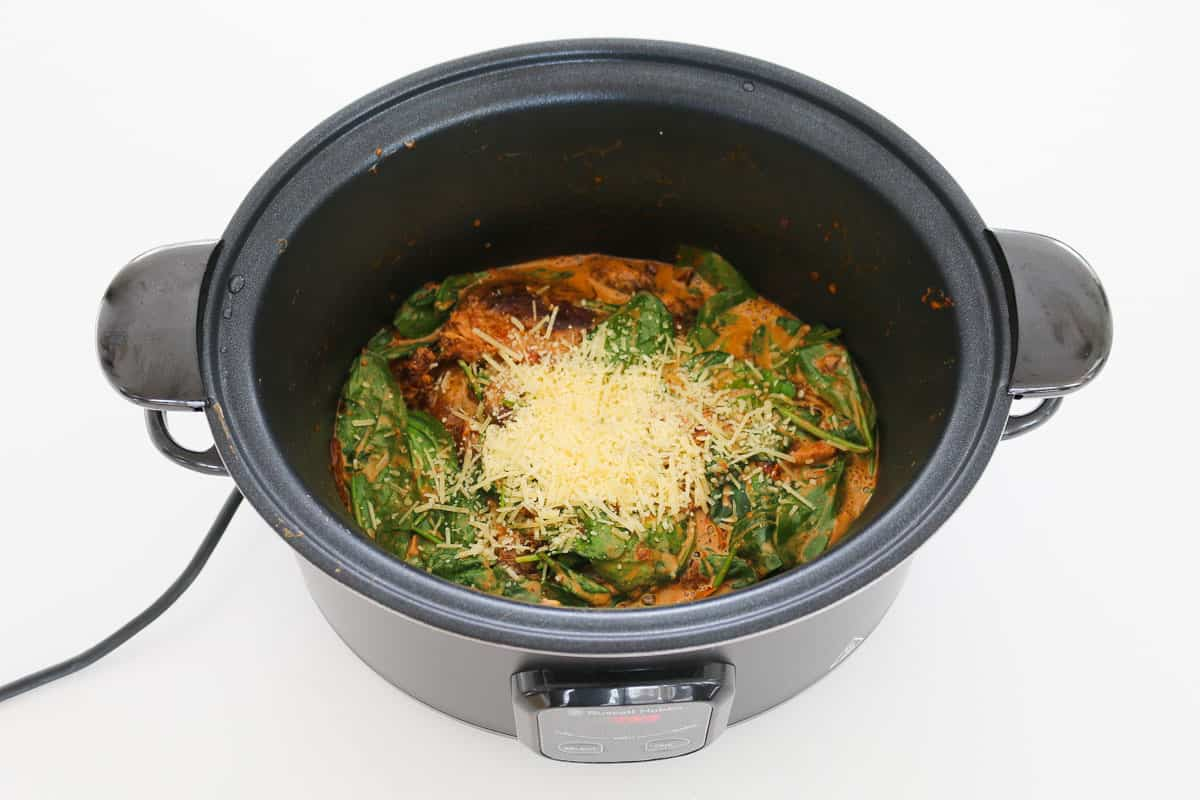 Parmesan cheese and spinach being added to a slow cooker.