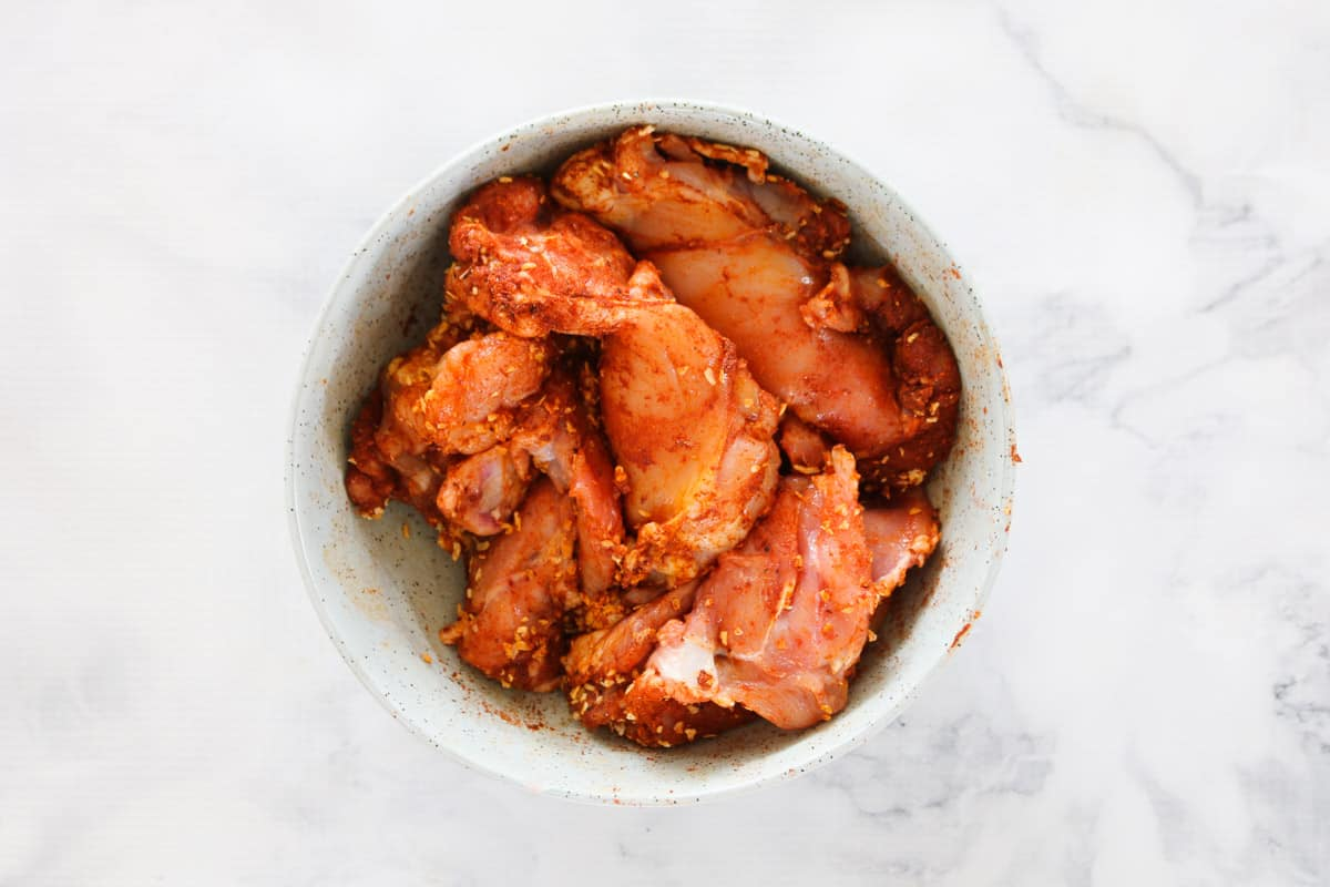 Paprika coated chicken in a bowl.