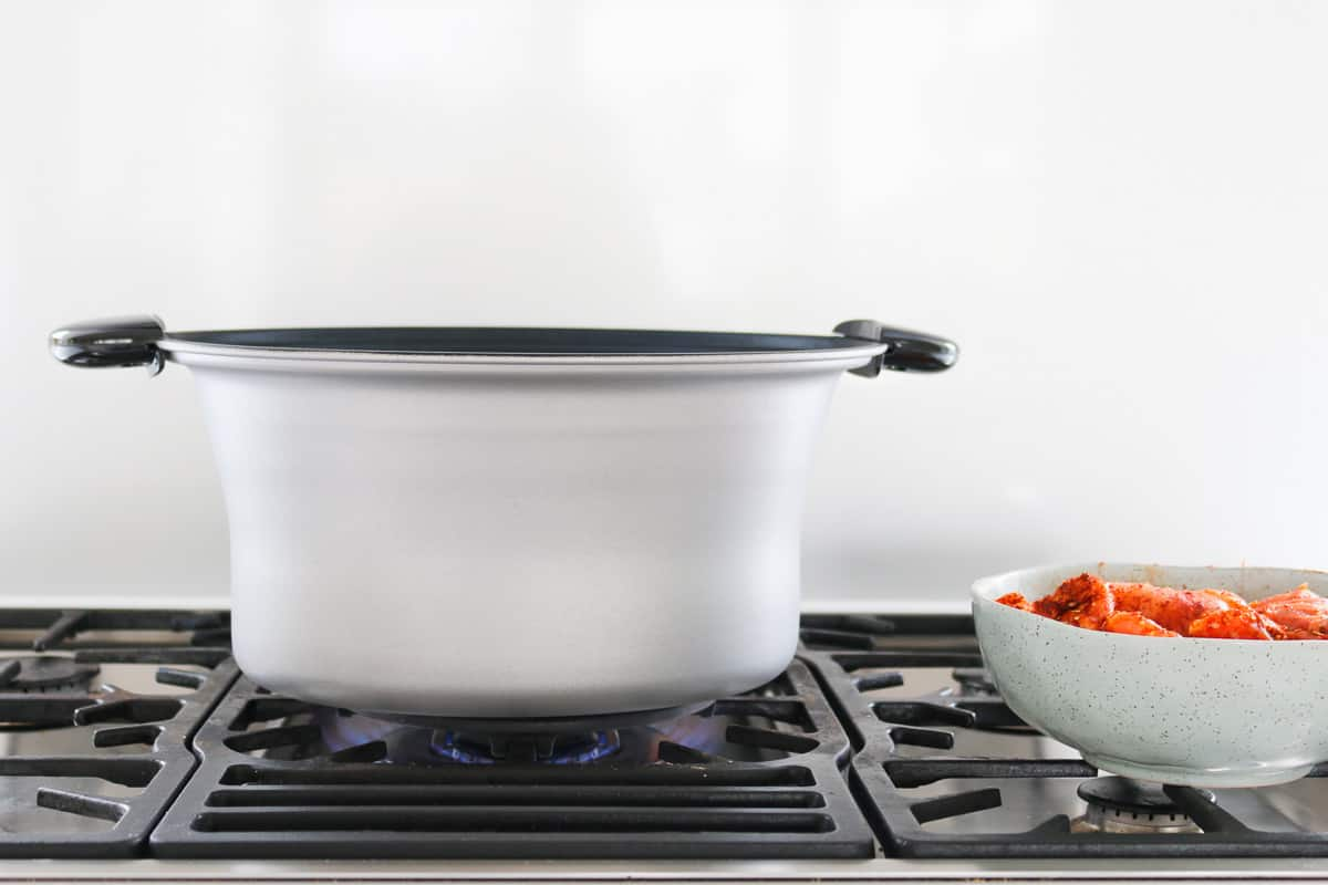 A crock pot bowl on the stove-top.
