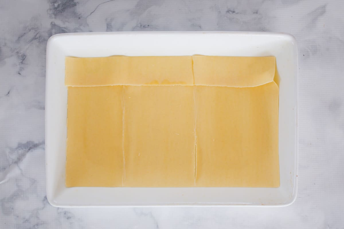 Fresh lasagne pasta sheets in a white baking dish.