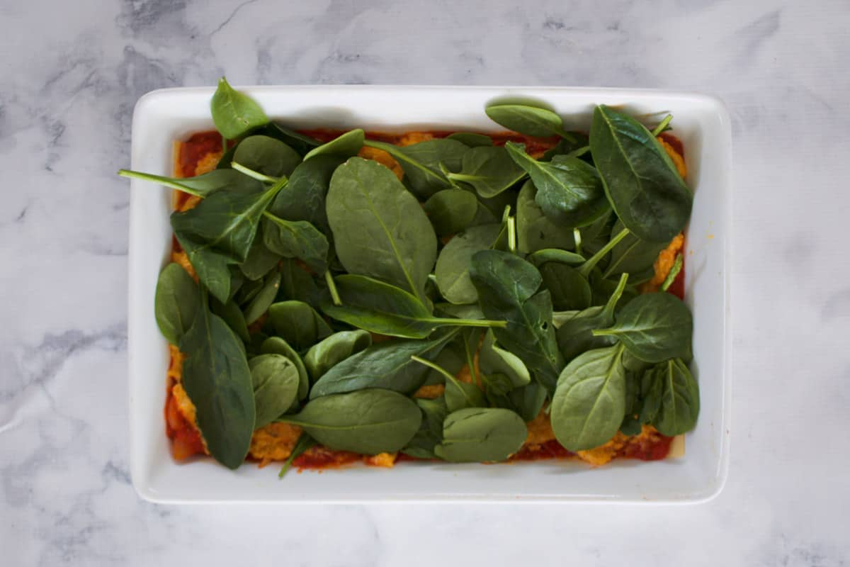 Baking spinach on top of pureed pumpkin in a baking dish.