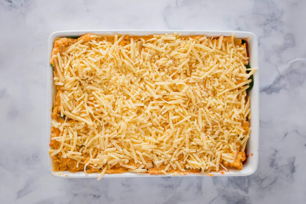 Grated cheese over the top of a pumpkin mixture in a rectangular baking dish.