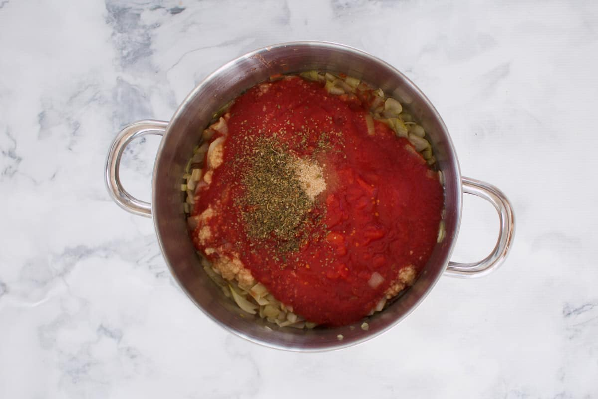 Insgredients for a tomato pasta sauce in a saucepan.