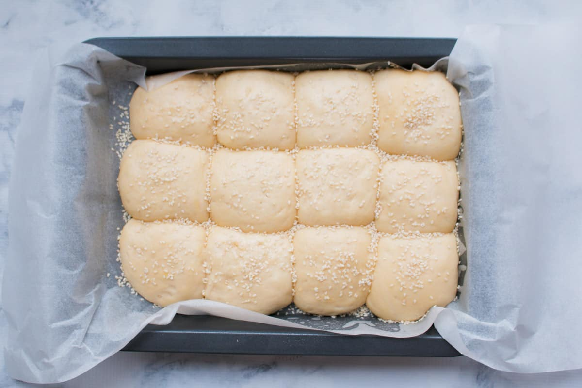 Bread roll dough balls in a baking tray.