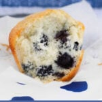A half-eaten sweet white muffin with blueberries mixed throughout.