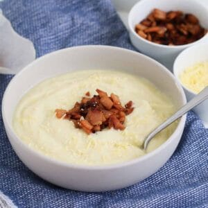 A bowl of creamy white soup with bacon and parmesan.