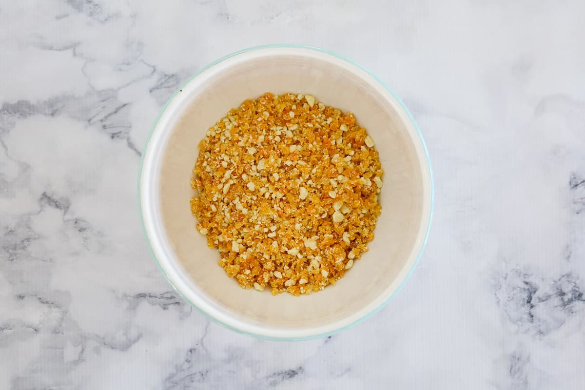 Finely chopped dried apricots and white chocolate in a white bowl.