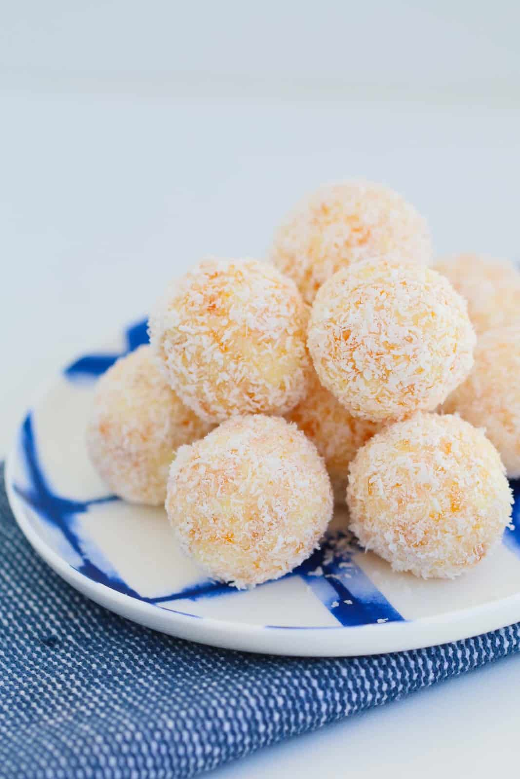Coconut and apricot balls on a white and blue plate.