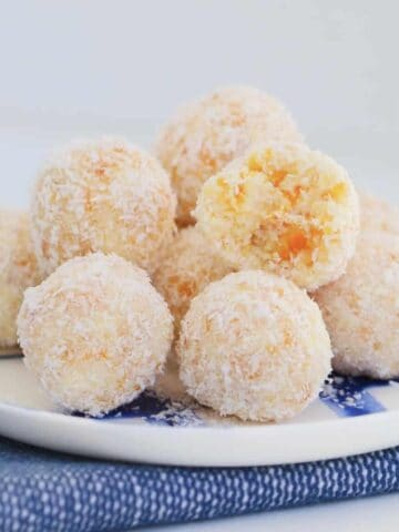 A blue and white striped plate topped with a pile of round balls covered in coconut.