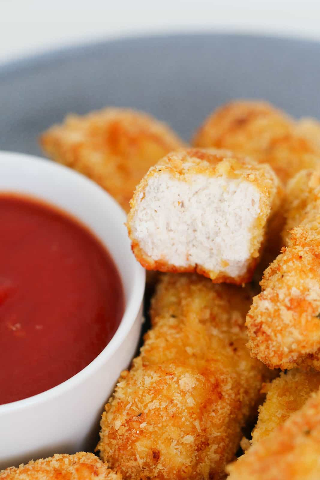 A half-eaten homemade chicken nugget with a bowl of red sauce.