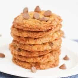A pile of oat cookies with chocolate chips on a white plate.