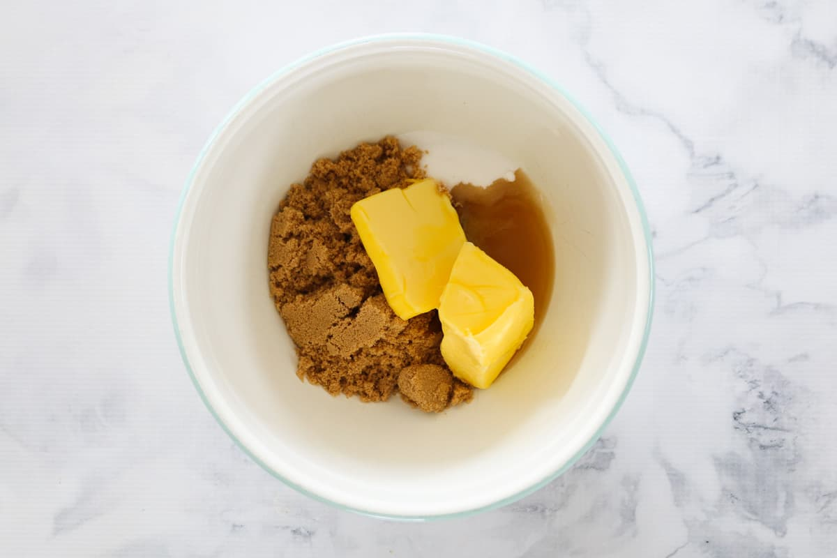 Butter, brown sugar and caster sugar in a white mixing bowl.