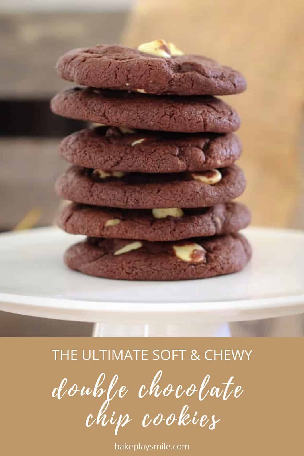 A stack of dark chocolate chip cookies with white chocolate chips on a white cake stand.