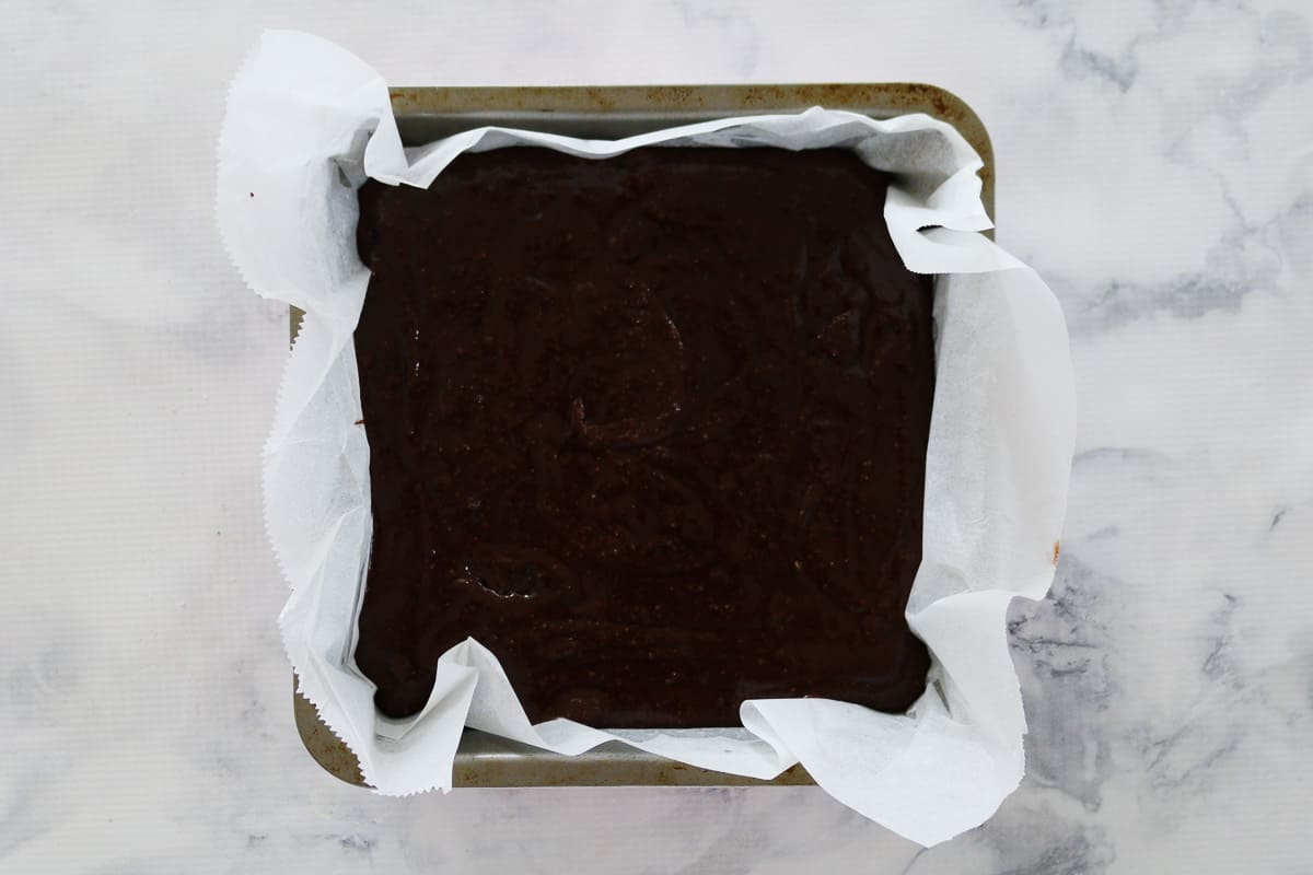 Brownie mixture in a square baking tin.