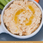 A bowl of hummus dip with olive oil drizzle and carrot and celery sticks in the background.
