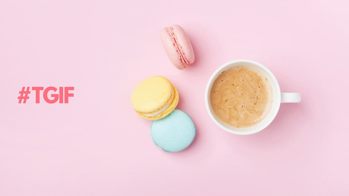 A cup of coffee with 3 colourful macarons on a pink background.