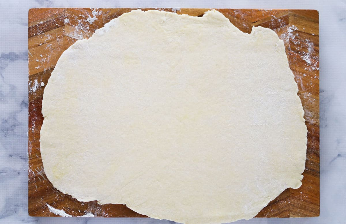 Dough rolled out on a wooden chopping board.
