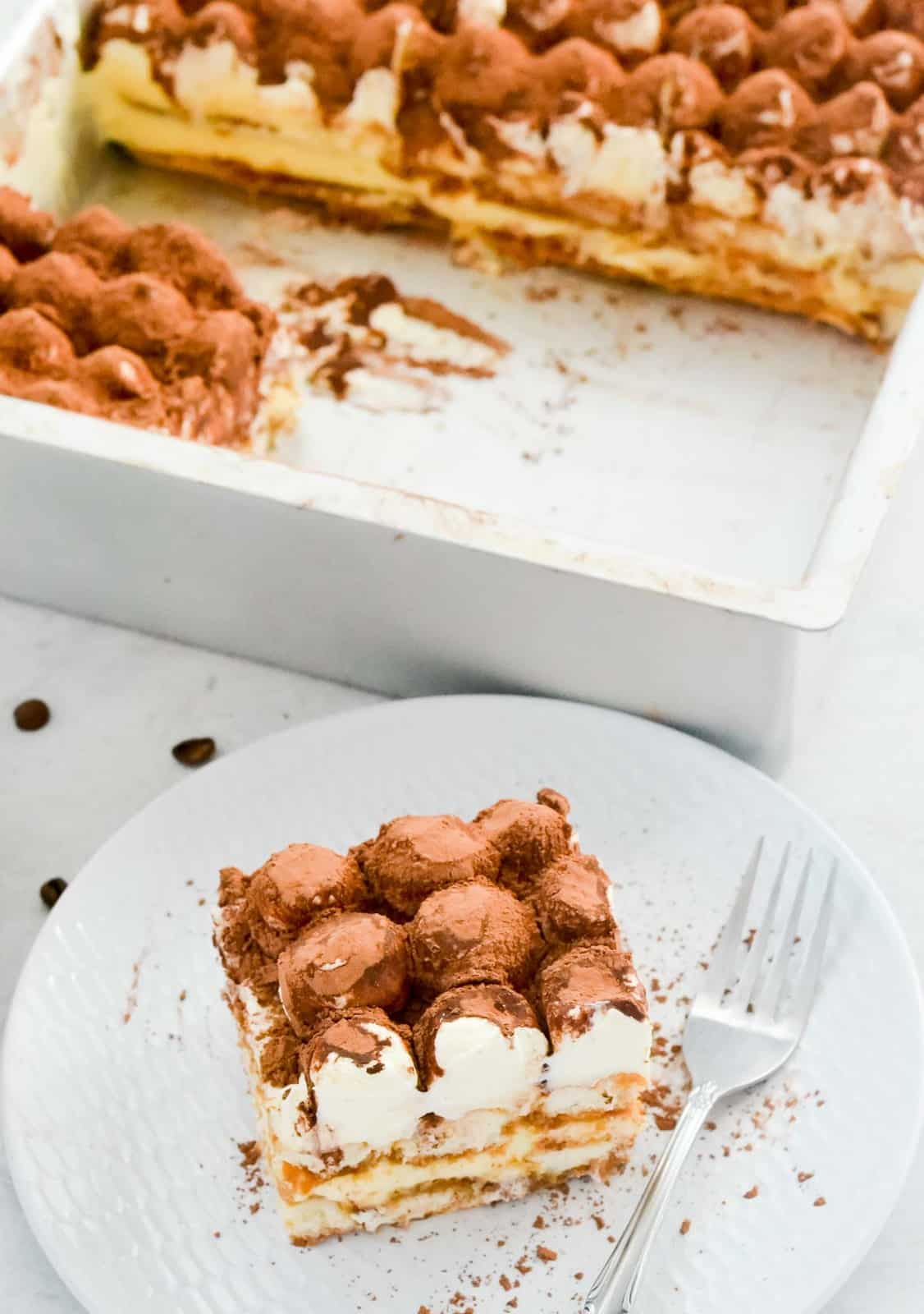 A tray of tiramisu with a piece removed on a plate.