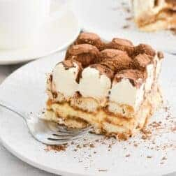 A piece of tiramisu on a plate with cocoa and whipped cream on top.