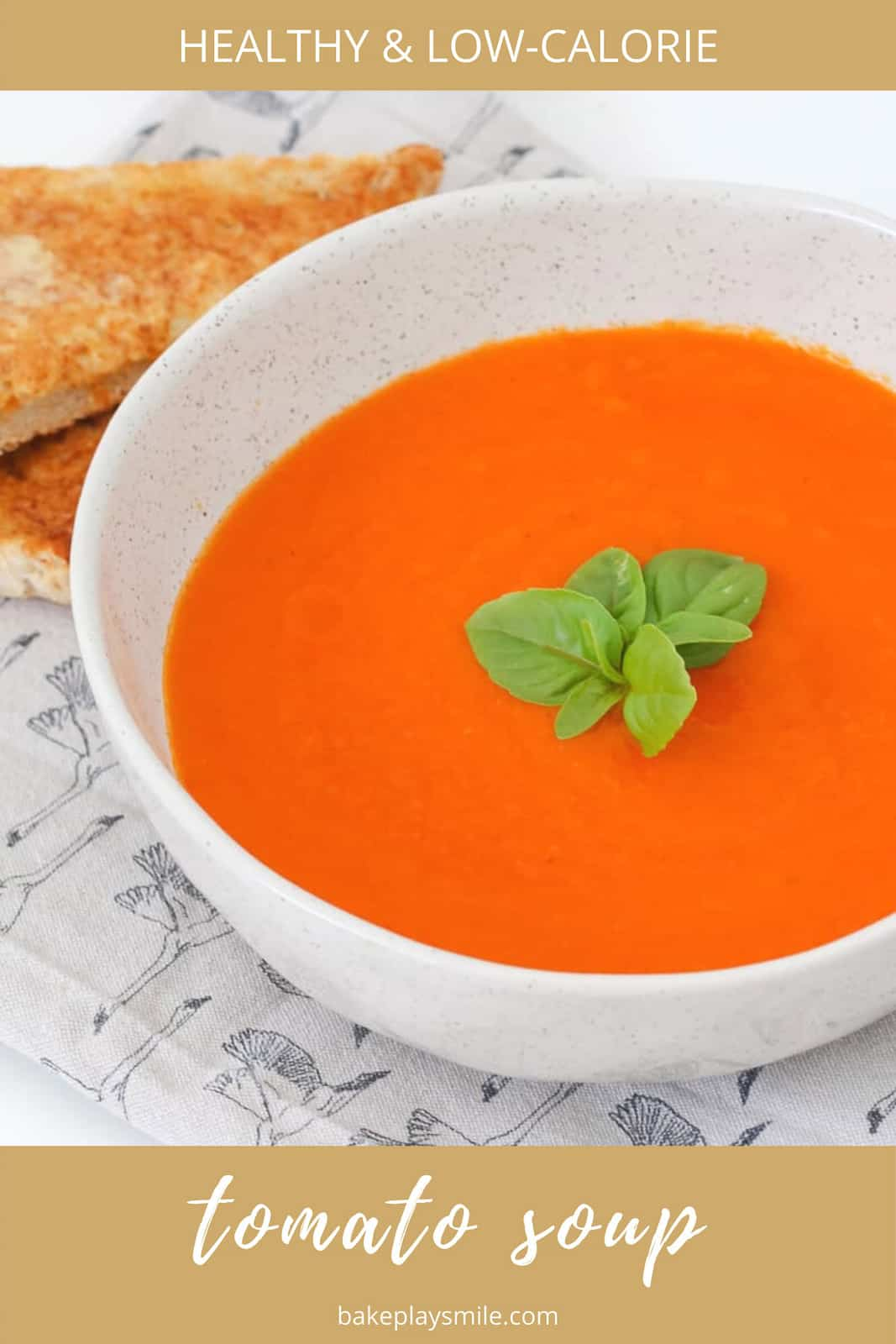 A bowl of pureed red vegetable soup with basil.
