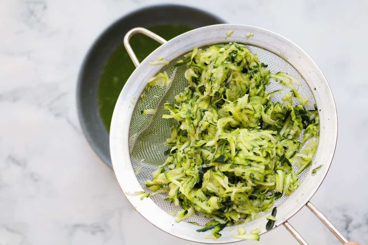 Grated zucchini in a strainer over a bowl.