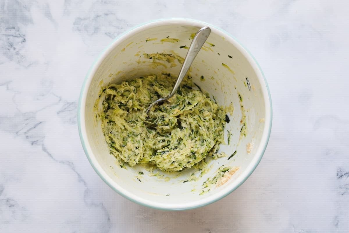 Grated zucchini and egg mixture in a bowl.
