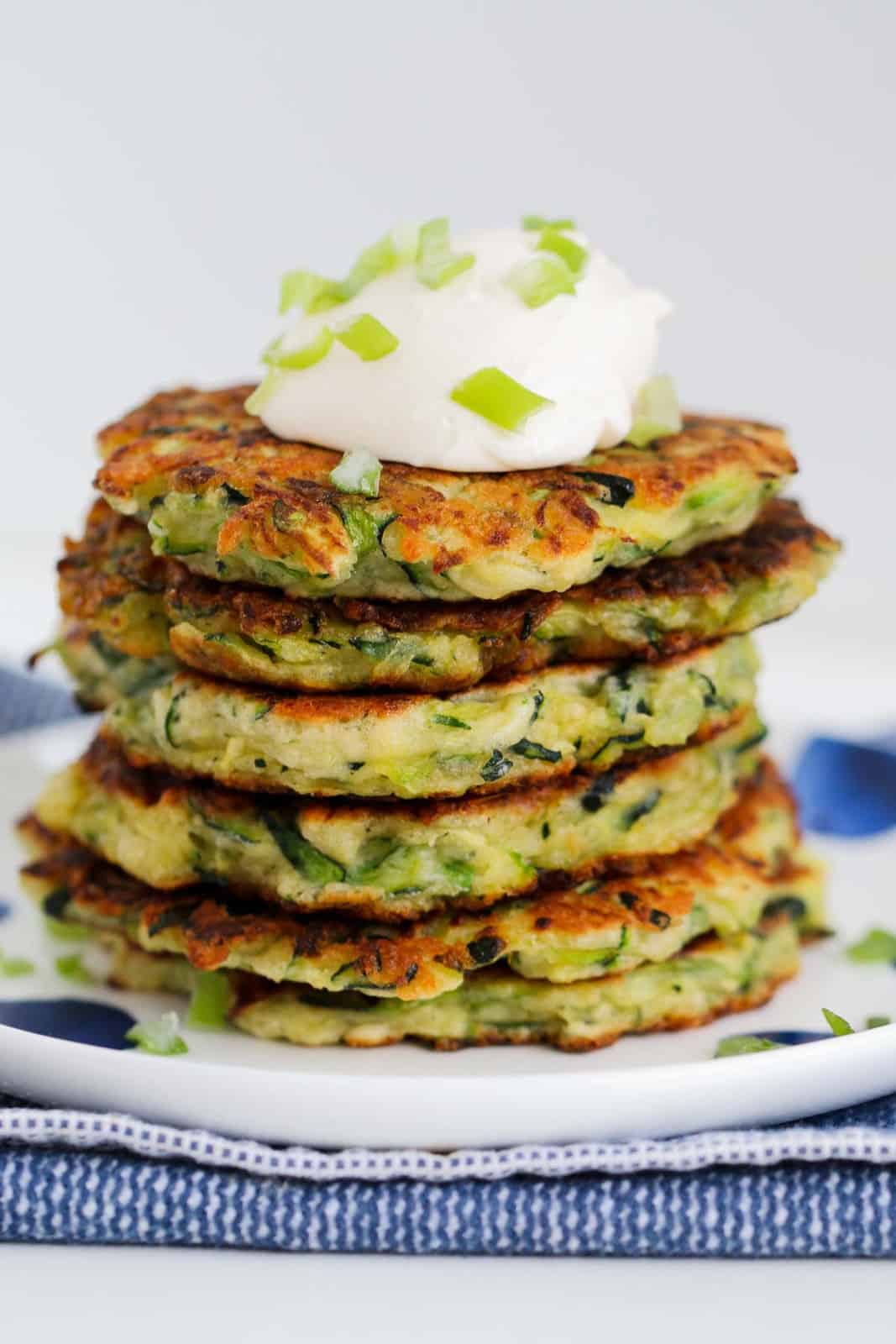 A stack of zucchini fritters with sour cream on top.