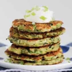 Six vegetable fritters in a stack with sour cream on top.