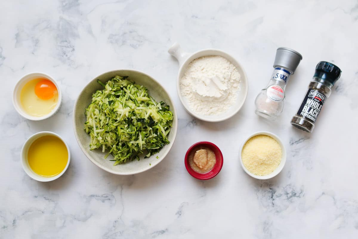 The ingredients for zucchini fritters on a marble background.