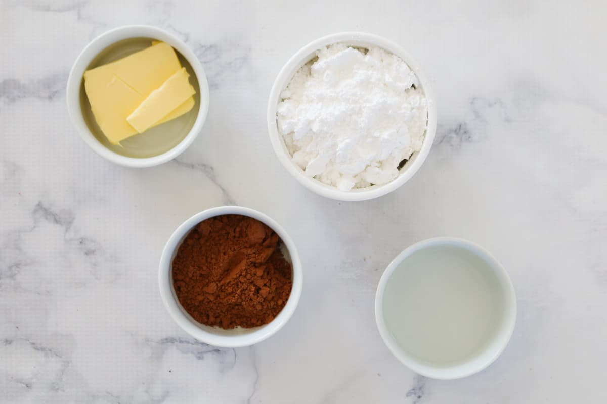 Cocoa, icing sugar, boiling water and butter in bowls on a marble background.