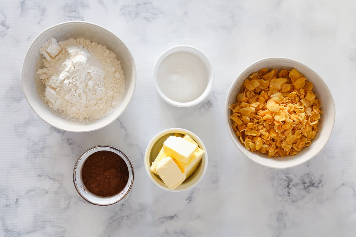 Cornflakes, cocoa powder, butter, flour and sugar in bowls on a marble background.