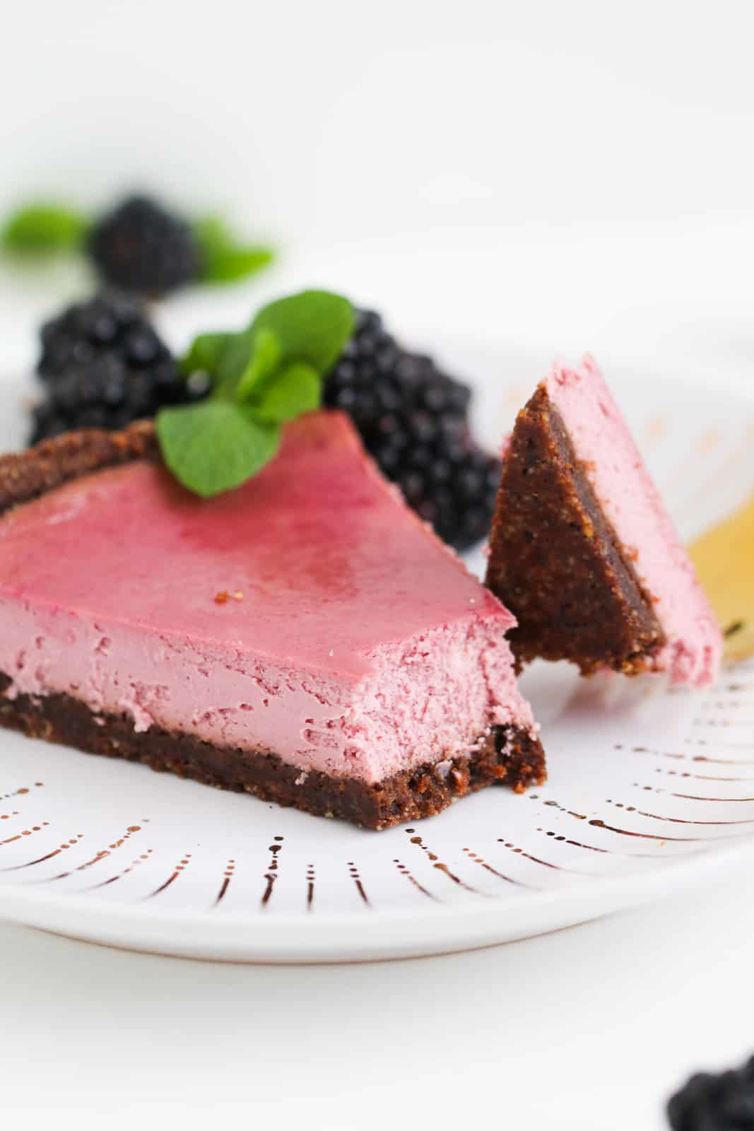 A slice of half-eaten berry cheesecake with fresh blackberries and mint leaves in the background.