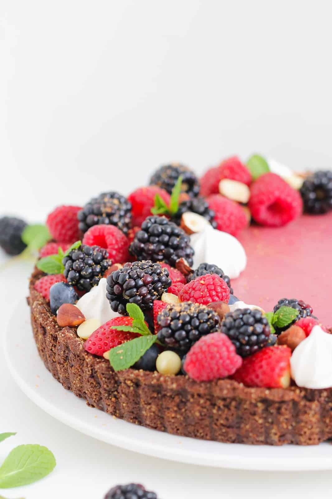 A berry tart with a chocolate base covered with fresh berries and mint leaves and meringues.