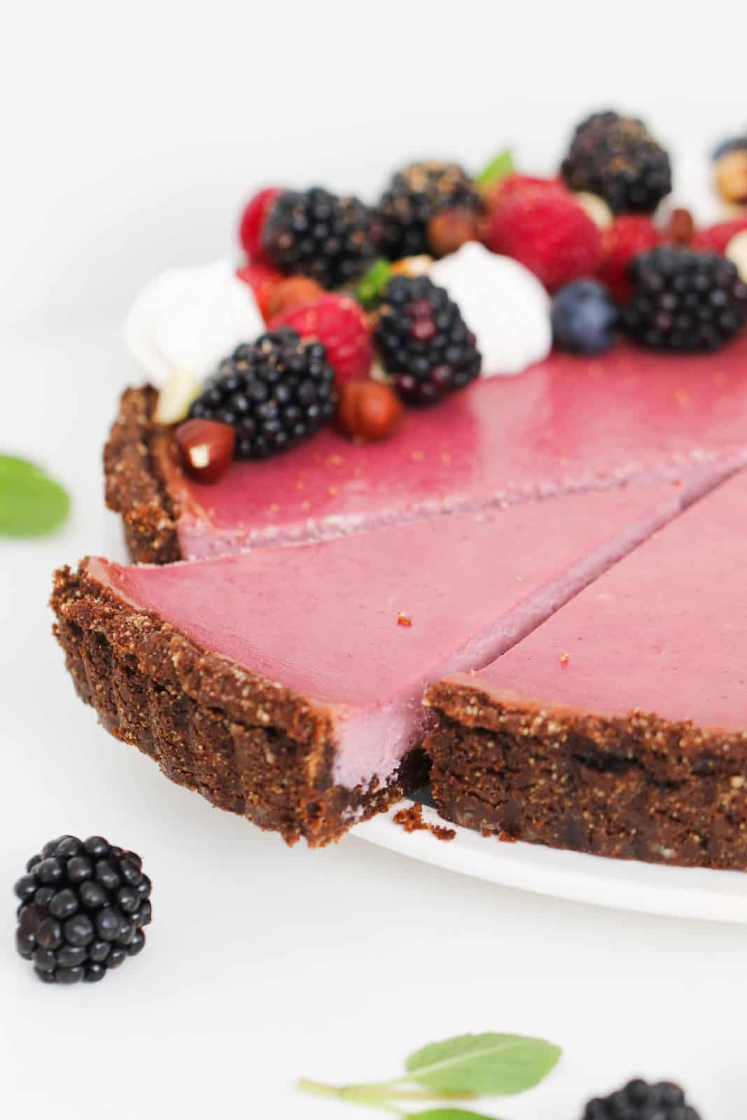 A slice of berry cheesecake being removed from a chocolate berry tart with fresh berries on top.
