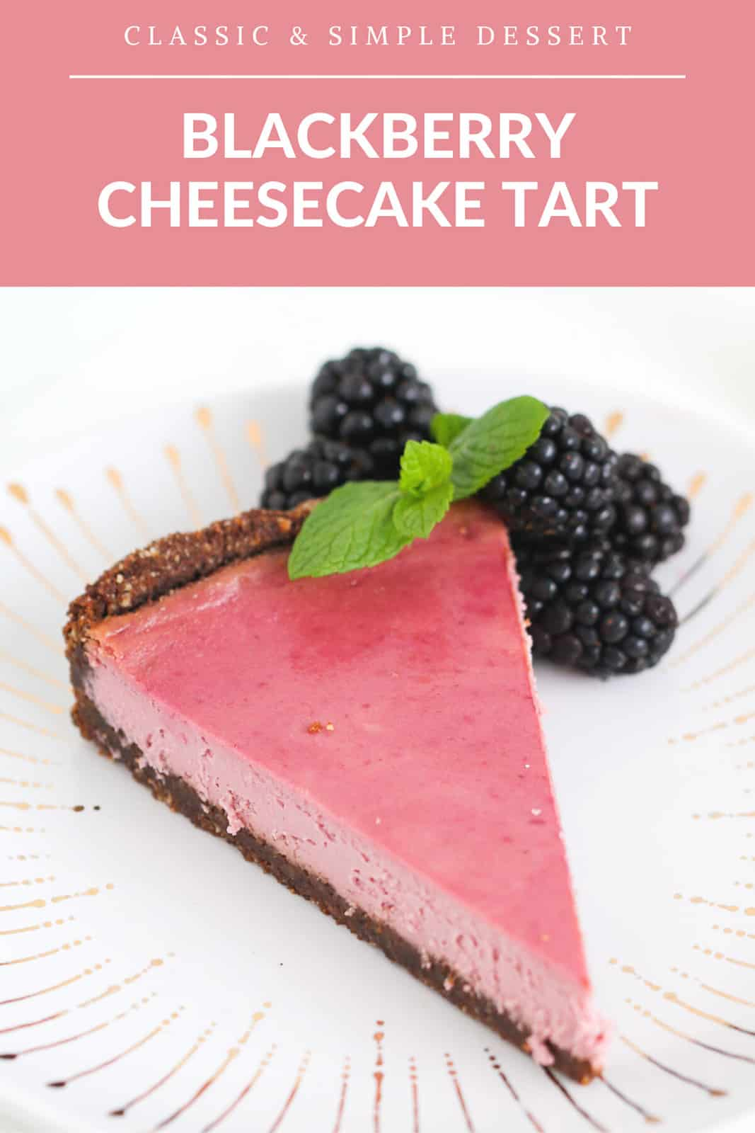 A slice of blackberry cheesecake tart on a white and gold plate with fresh blackberries and mint leaves.