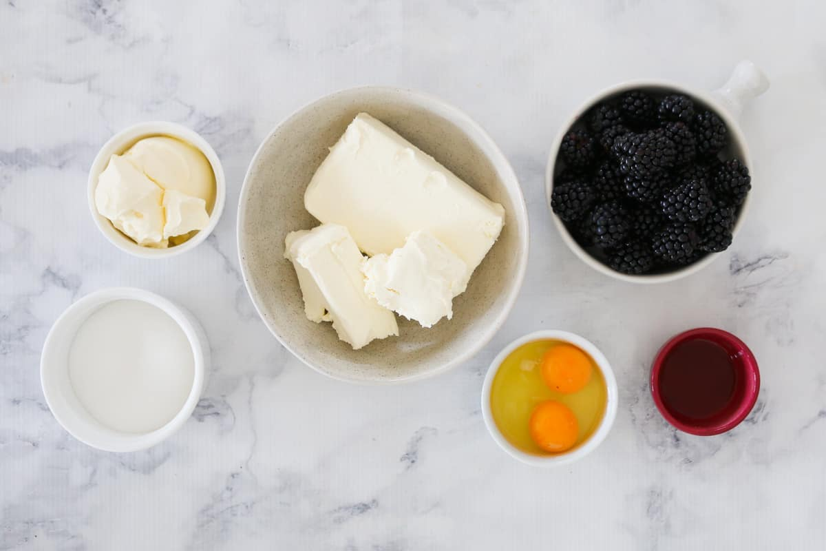 The ingredients for a blackberry cheesecake in bowls on a marble background.