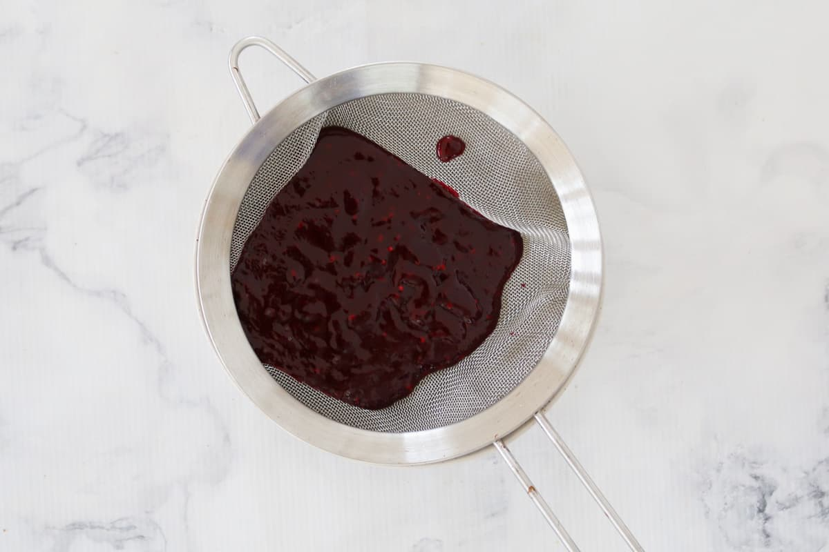Blackberry puree in a silver metal strainer.