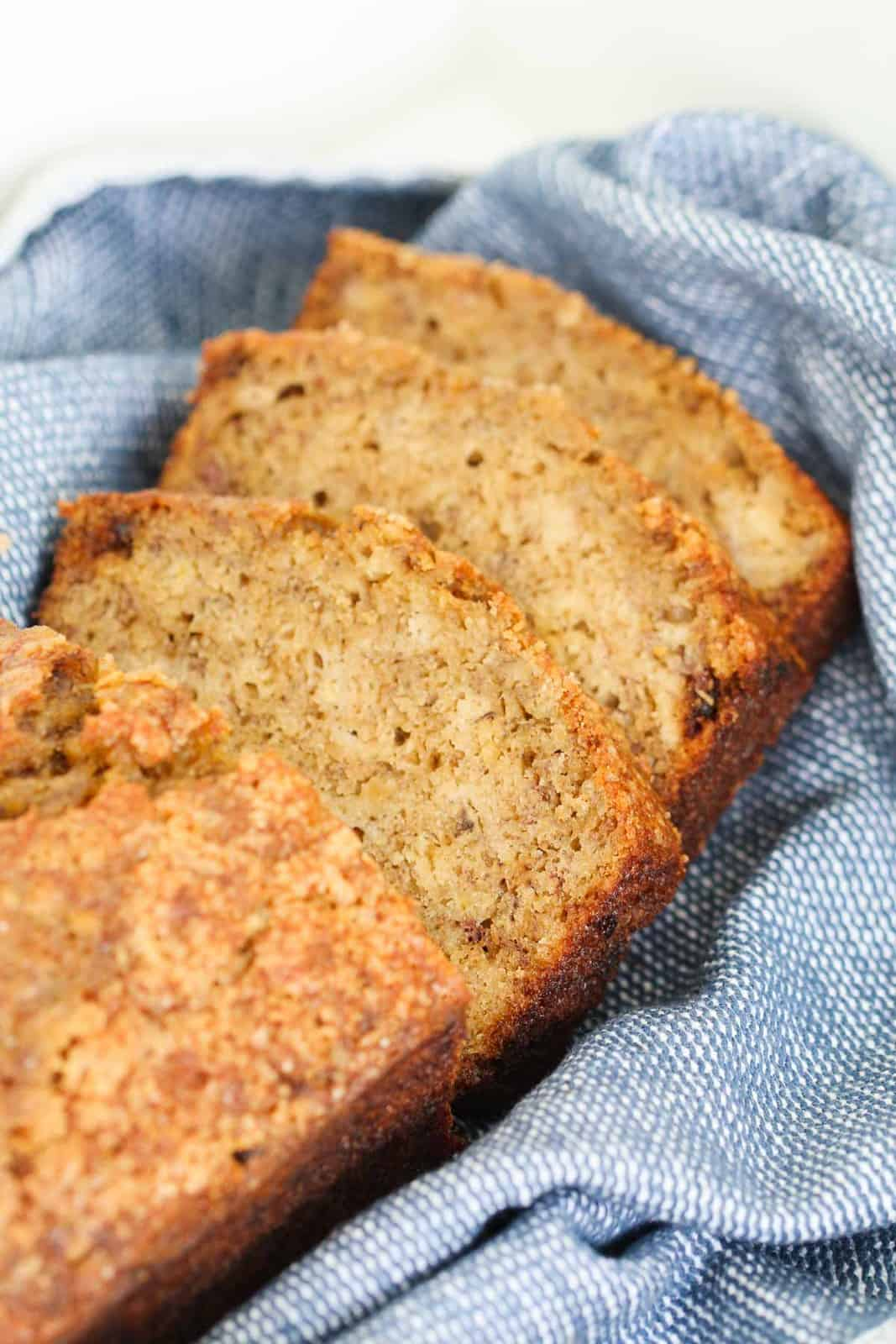 Slices of banana bread on a blue tea towel.
