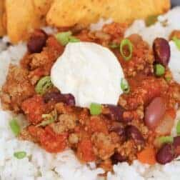 A bowl of rice rice, slow cooker chilli con carne, sour cream and corn chips.