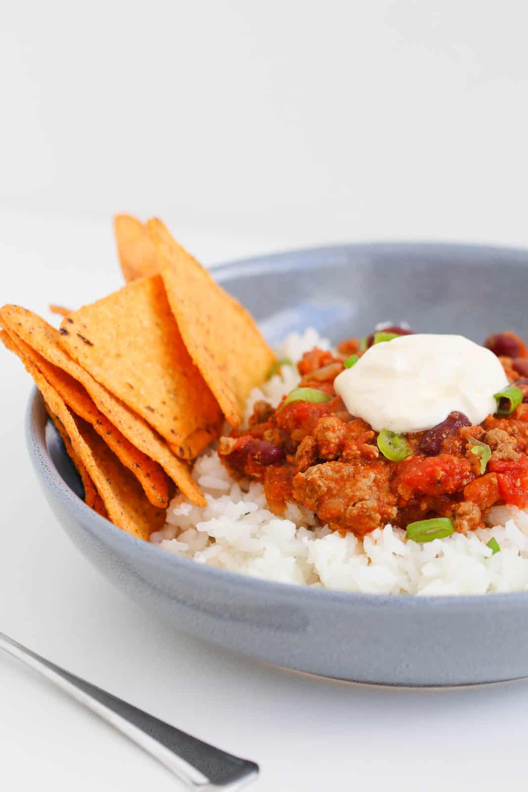 Corn chips in a bowl of slow cooker chilli con carne with rice, spring onions and sour cream.