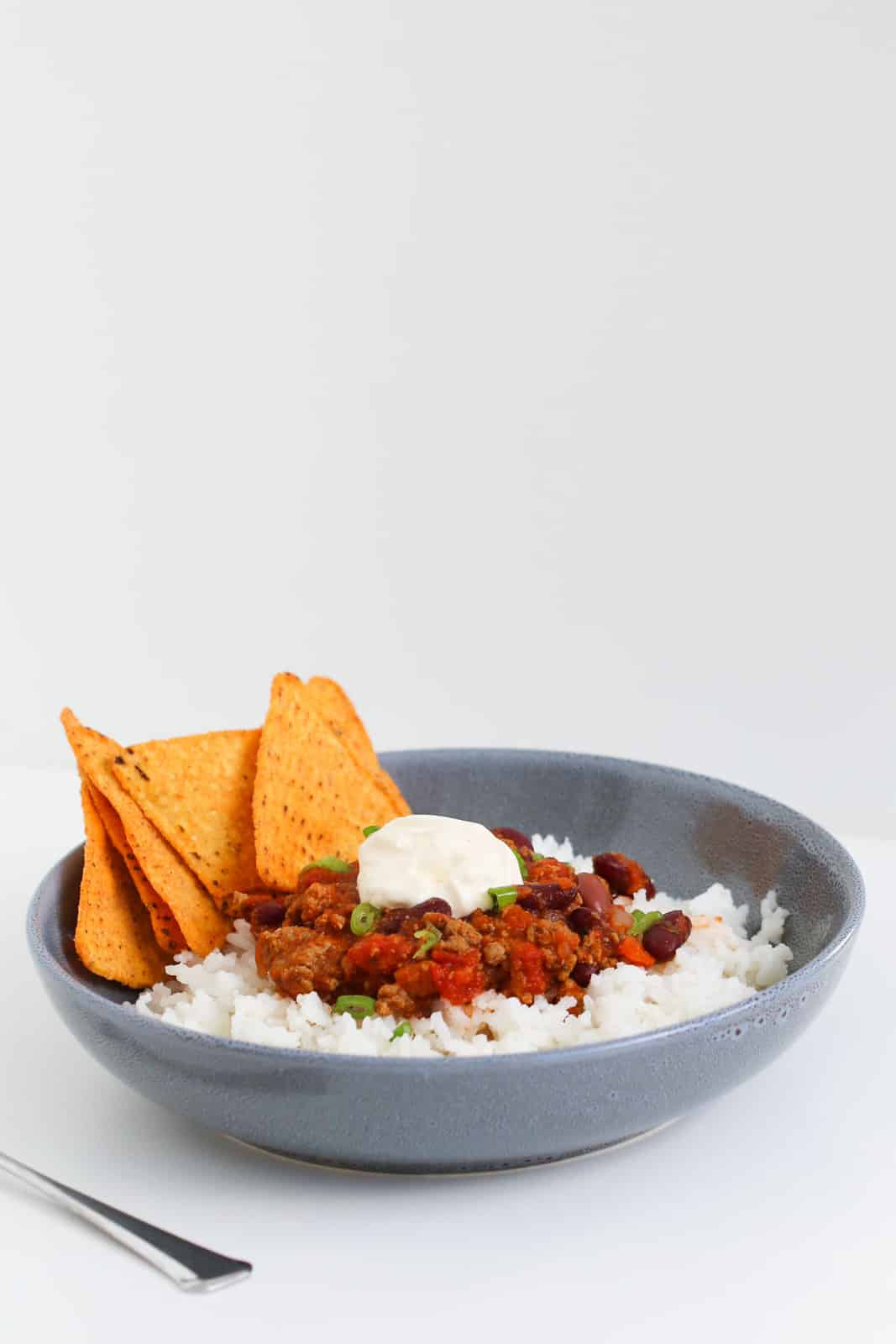 A blue bowl filled with chilli con carne, corn chips, sour cream, rice and spring onions.