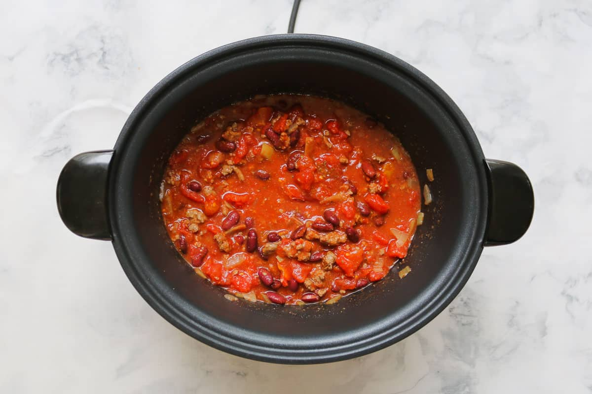 Tomato, spices, beef and onion in a slow cooker.