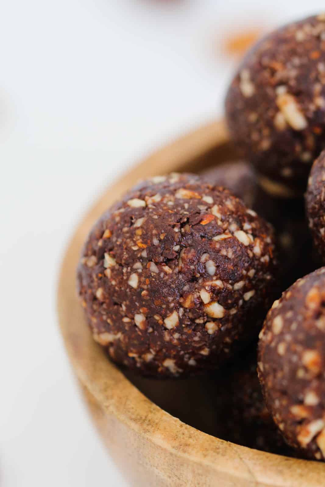 A close up shot of a round date, almond and chocolate protein ball showing nutty texture.