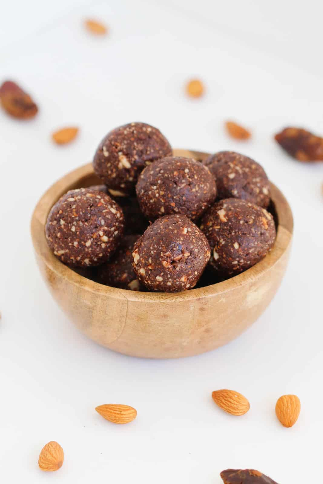 Almond, date and chocolate protein balls in a wooden bowl on a white bench.
