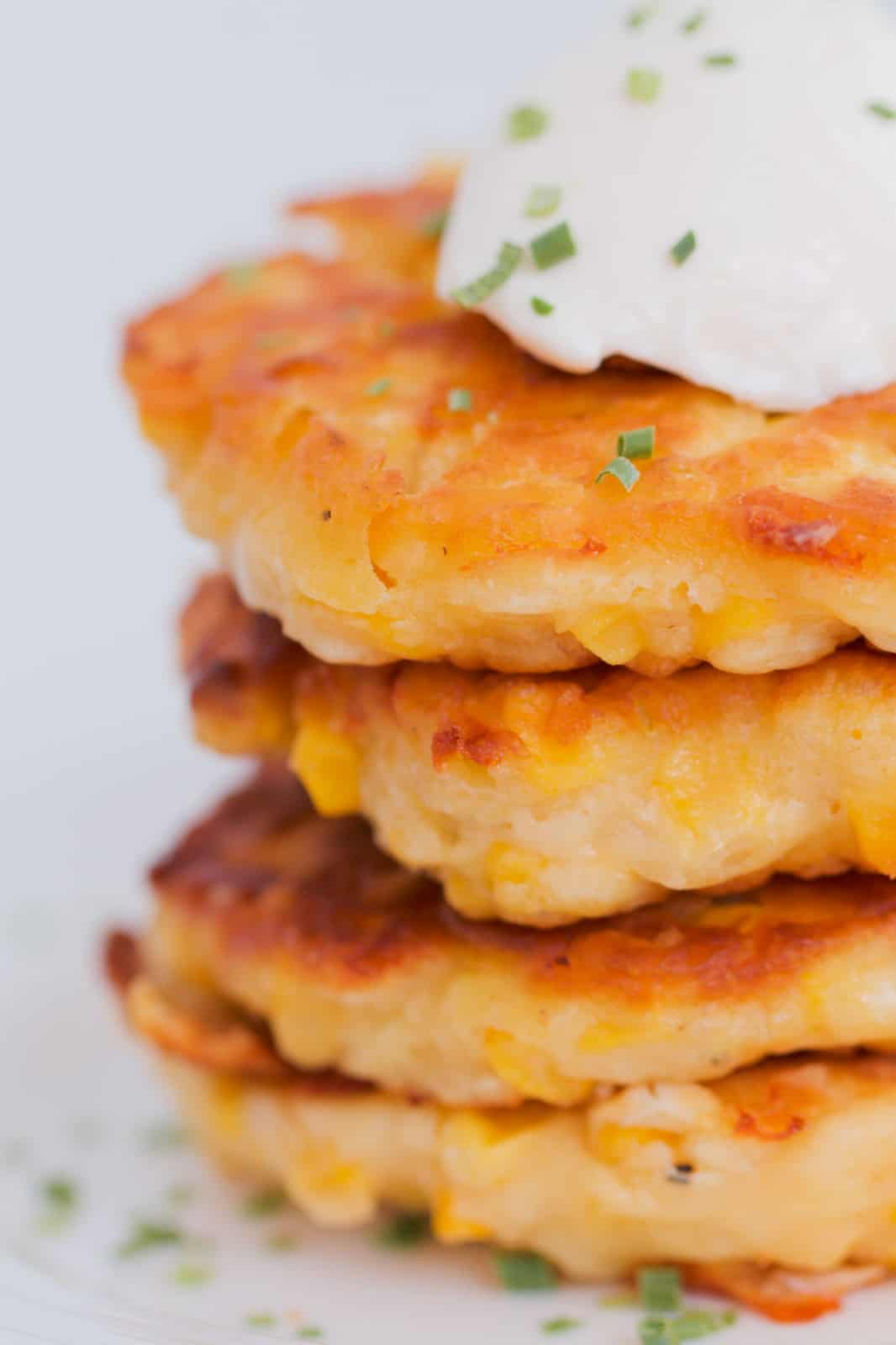 A close up shot of crispy corn fritters topped with sour cream and chives.