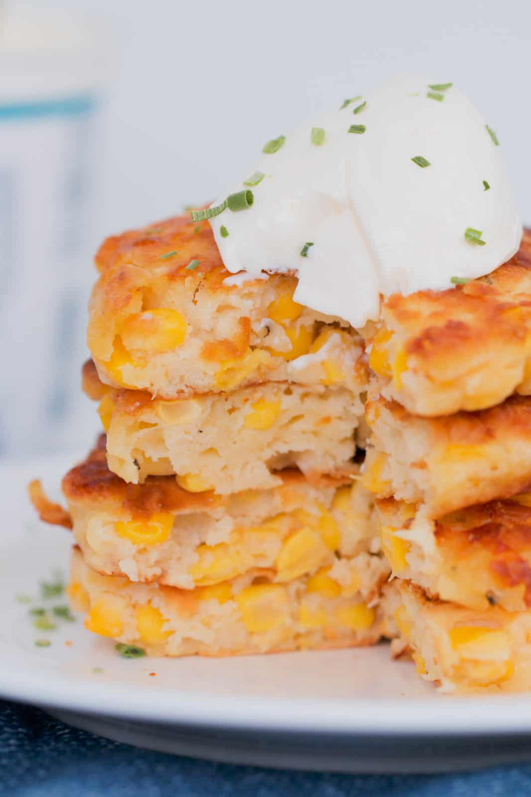 Fluffy corn fritters, cut through the middle with sour cream and chives on top.